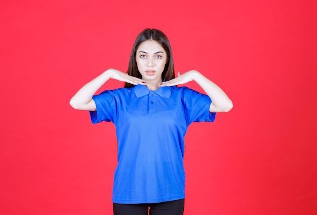 Vrouw in blauw shirt staande op rode muur.
