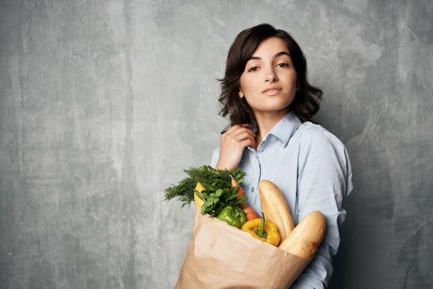 Vrouw in blauw shirtpakket met bezorggroenten voor supermarktboodschappen