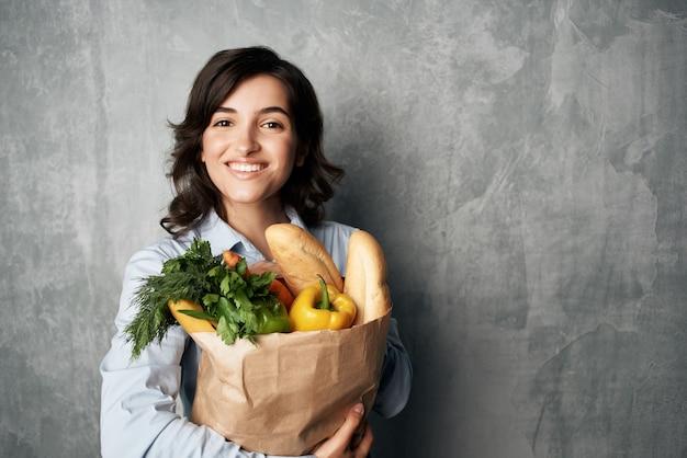 Vrouw in blauw shirtpakket met boodschappen in het voedseldieet van de supermarkt