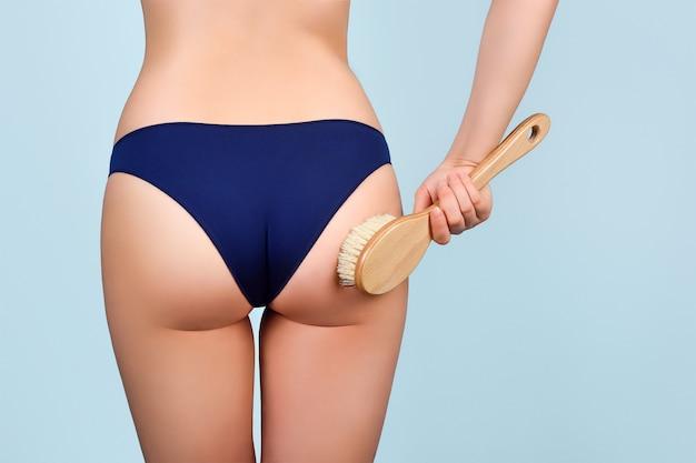 Vrouw in blauw slipje houdt een cactusborstel vast voor een droge massage tegen cellulitis