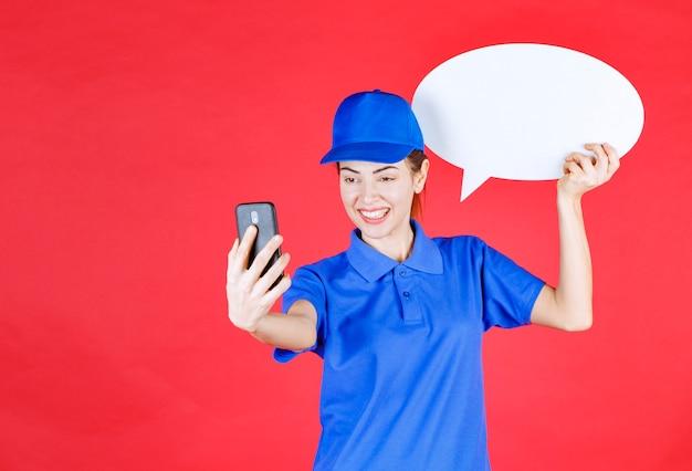 Vrouw in blauw uniform die een ovale ideeënbord vasthoudt en een videogesprek voert.