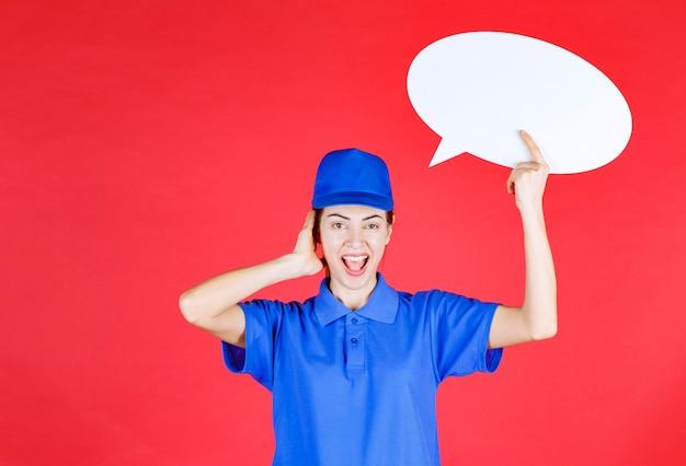 Vrouw in blauw uniform die een ovale ideeënbord vasthoudt en haar oor wijst om goed te horen.