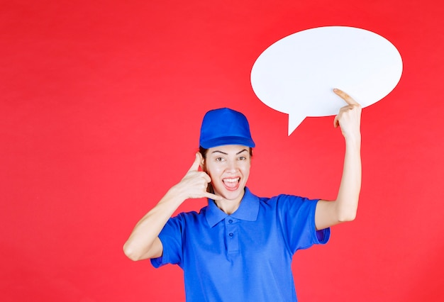 Vrouw in blauw uniform die een ovale ideeënbord vasthoudt en om een telefoontje vraagt.