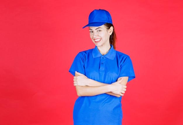 Vrouw in blauw uniform die positieve en neutrale poses geeft.