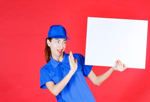 Vrouw in blauw uniform en baret die een wit vierkant infobureau vasthoudt en iets weigert.