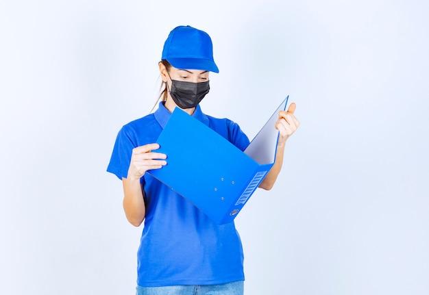 Vrouw in blauw uniform en zwart gezichtsmasker die een blauwe map opent en controleert.