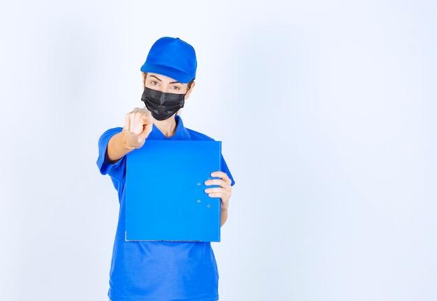 Vrouw in blauw uniform en zwart gezichtsmasker die een blauwe map vasthoudt en naar iemand opzij wijst.
