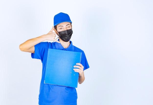 Vrouw in blauw uniform en zwart gezichtsmasker die een blauwe map vasthoudt en om een oproep vraagt.