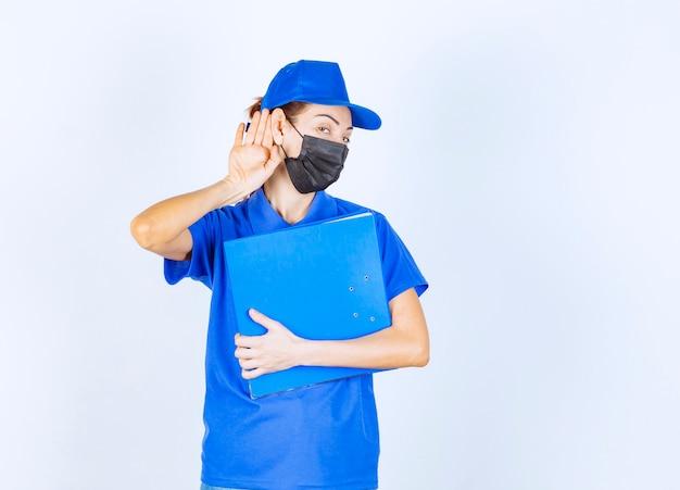 Vrouw in blauw uniform en zwart gezichtsmasker die een blauwe map vasthoudt en oor opent om goed te horen.