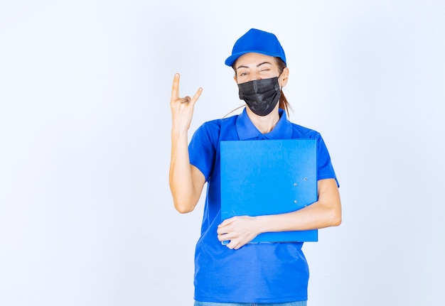 Vrouw in blauw uniform en zwart gezichtsmasker met een blauwe map en voelt zich positief en vriendelijk.