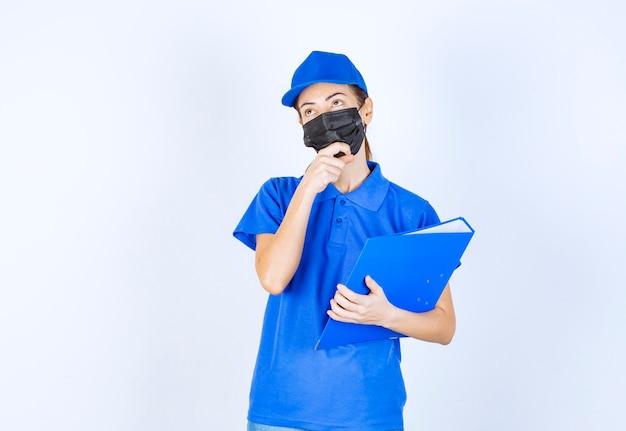 Vrouw in blauw uniform en zwart gezichtsmasker met een blauwe map en ziet er verward en attent uit.
