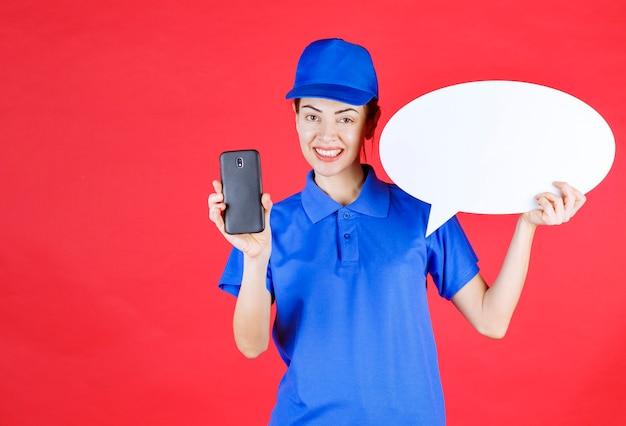Vrouw in blauw uniform met een ovale ideeënbord en een mobiele telefoon.