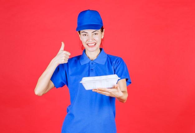 Vrouw in blauw uniform met een witte plastic afhaaldoos voor bezorging en tevredenheidsteken.