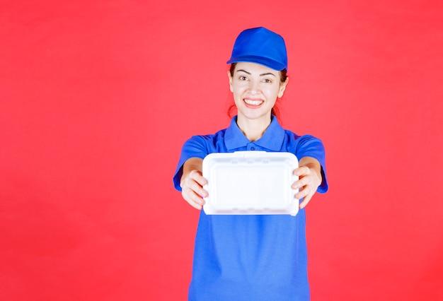 Vrouw in blauw uniform met een witte plastic afhaaldoos voor bezorging.