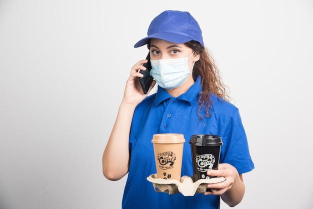 Vrouw in blauw uniform met medisch masker die telefonisch spreekt en twee kopjes koffie op wit houdt