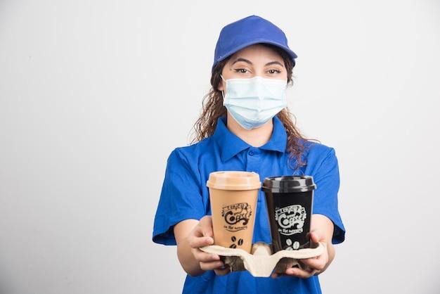 Vrouw in blauw uniform met medisch masker met twee kopjes koffie op wit