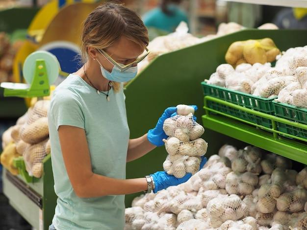 Vrouw in blauwe handschoenen en gezichtsmasker die een knoflook in kruidenierswinkelopslag kiezen tijdens pandemisch coronavirus covid-19.