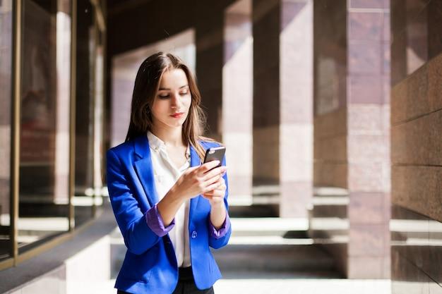 Vrouw in blauwe jas controleert haar telefoon
