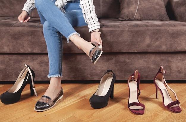 Vrouw in blauwe jeans die en schoenen thuis kiezen probeert.