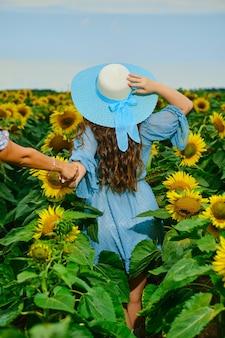 Vrouw in blauwe jurk en hoed met brede rand houdt de hand van een vriend vast die door zonnebloemveld loopt. volg mij gebaar.