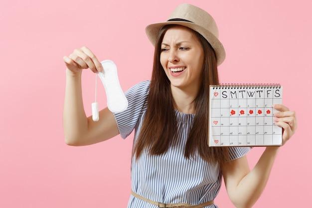 Vrouw in blauwe jurk, hoed met maandverband, tampon vrouwelijke menstruatiekalender, menstruatiedagen controleren geïsoleerd op roze achtergrond. medisch, gezondheidszorg, gynaecologisch keuzeconcept. ruimte kopiëren.