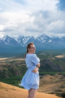 Vrouw in blauwe jurk in de zomer altai bergen in kurai steppe