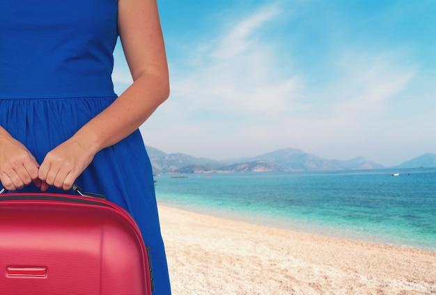 Vrouw in blauwe jurk met bagage close-up op blured strand achtergrond