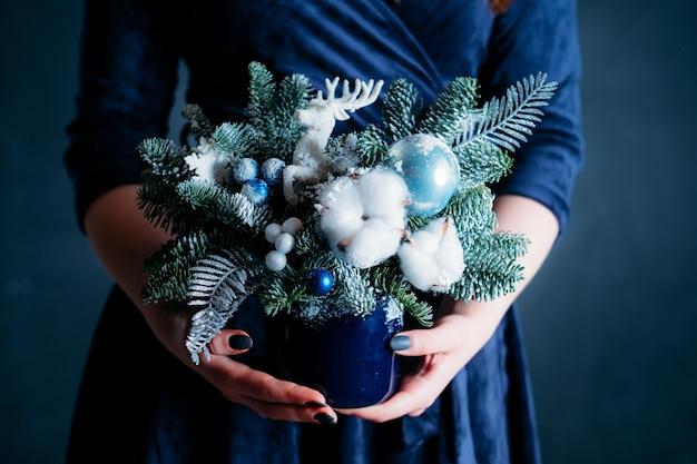 Vrouw in blauwe jurk met handgemaakte dennenboom arrangement met herten, katoen, nepsneeuw.