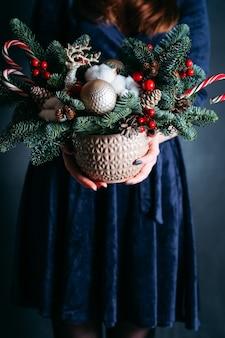 Vrouw in blauwe jurk met pot met dennenboom, herten, zuurstokken.
