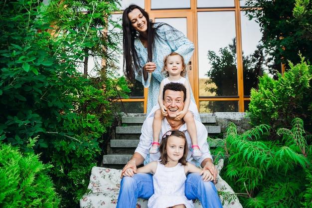 Vrouw in blauwe jurk staat achter haar dochters en grappige echtgenoot in voetstappen