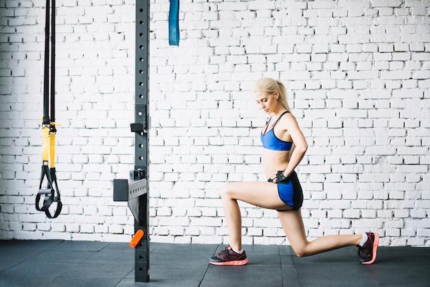 Vrouw in blauwe sportkleding doet lunges