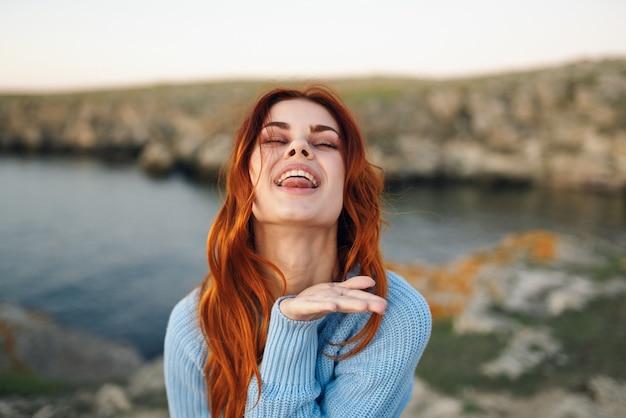 Vrouw in blauwe trui buitenshuis frisse lucht rotsachtige bergen landschap