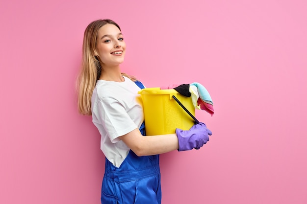 Vrouw in blauwe werk uniforme stand met emmer en vodden poseren geïsoleerd op roze achtergrond