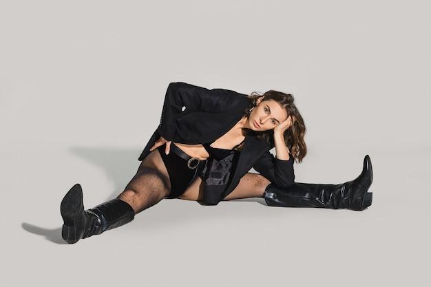 Vrouw in blazer en leren laarzen zit op de vloer in de studio en strekt haar benen