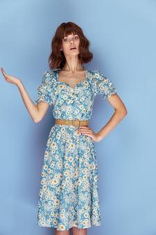 Vrouw in bloem jurk verrast gezichtsuitdrukking handgebaren zomer kleding levensstijl