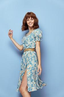 Vrouw in bloem vrolijke glimlach handgebaar blauwe muur jurk stijlvolle kleding zomerkleding