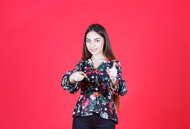 Vrouw in bloemenoverhemd die zich op rode muur bevindt en de persoon vooruit opmerkt.