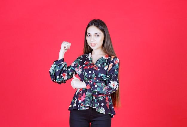 Vrouw in bloemenoverhemd die zich op rode muur bevindt en haar wapenspieren demonstreert.