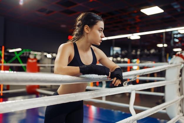 Vrouw in boksbandages aan de touwen in de ring