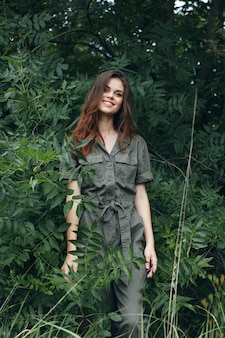Vrouw in bos mooie glimlach in groene jumpsuit reizen bijgesneden weergave