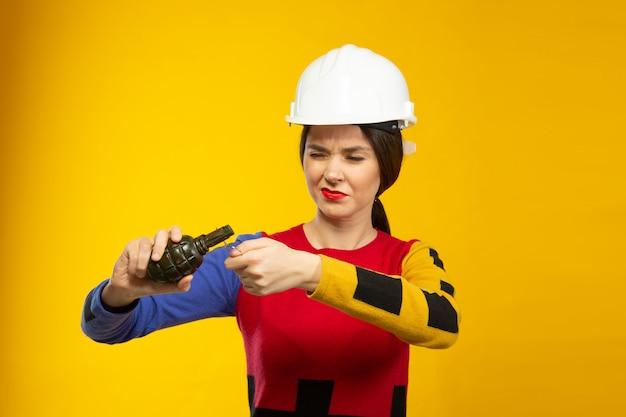 Vrouw in bouwhelm met handgranaatreplica