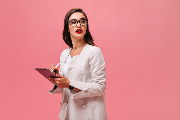 Vrouw in bril maakt aantekeningen in tablet. mooie brunette met grote rode lippen in licht pak poseren op geïsoleerde achtergrond.
