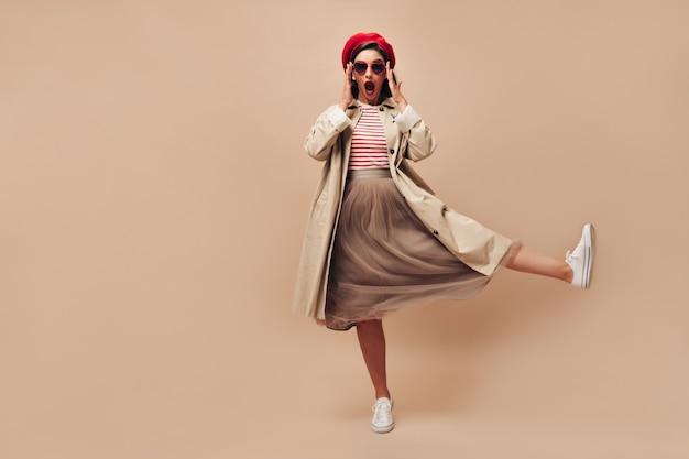 Vrouw in brillen verrast kijkt naar camera op beige achtergrond. stijlvol meisje in zonnebril in vorm van hart en in lange rok heft haar been op.