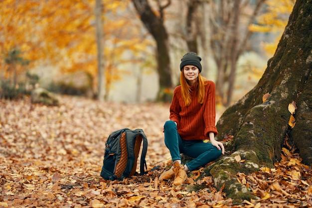 Vrouw in broek en laarzen met een rugzak zit in de buurt van een boom in de herfst bos gevallen bladeren