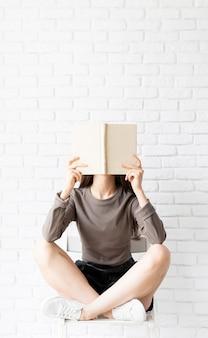 Vrouw in bruin shirt zittend op de stoel met gekruiste benen met een geopend boek