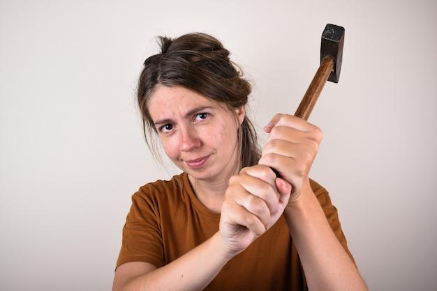 Vrouw in bruin t-shirt, met hamer, geïsoleerd. huis renovatie concept