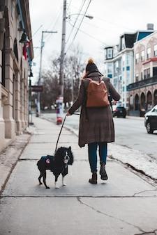 Vrouw in bruine jas en blauwe rok lopen met zwarte hond op de stoep overdag