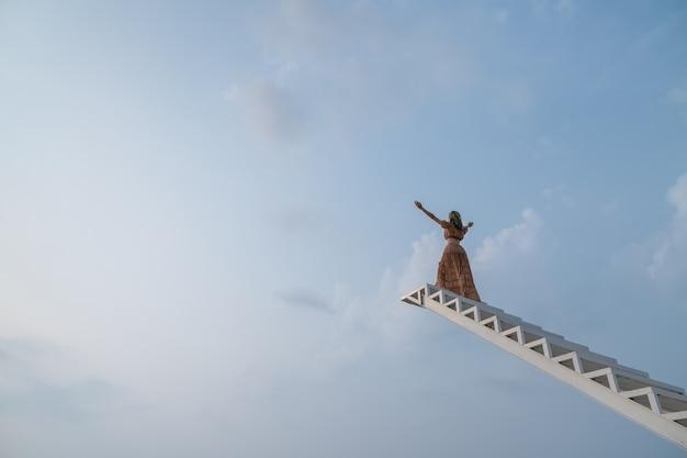 Vrouw in bruine jurk, handen omhoog lopen op de trap. vrijheid voelt goed.
