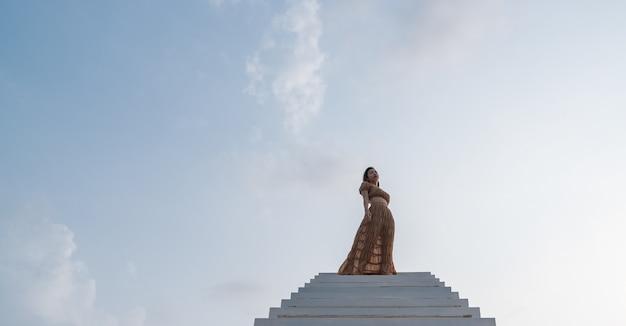 Vrouw in bruine jurk staande op de trap.