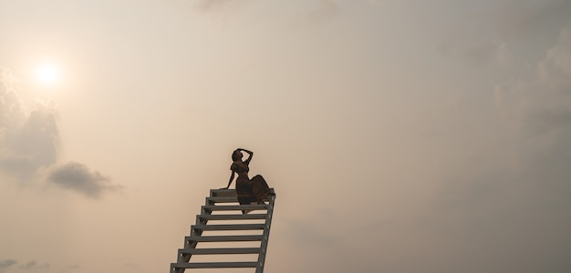 Vrouw in bruine jurk zittend op de trap, zonsondergang moment.